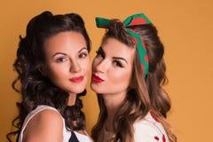 Duas mulheres bonitas nos vestidos levantam no estúdio alaranjado Imagens de Stock Royalty Free