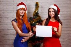 Duas mulheres bonitas novas em Santa tampam mostrar os polegares acima do gestur fotos de stock