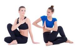 Duas mulheres bonitas novas na pose da ioga isoladas no branco Imagens de Stock
