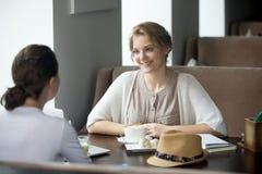 Duas mulheres bonitas novas que bebem o café no café imagem de stock