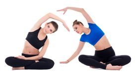 Duas mulheres bonitas novas que fazem esticando os exercícios isolados sobre Imagens de Stock