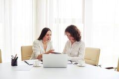 Duas mulheres bonitas novas que trabalham junto com dispositivos no offi Imagem de Stock