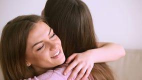Duas mulheres bonitas que abraçam, aperto dos amigos próximos, rindo tendo o divertimento vídeos de arquivo