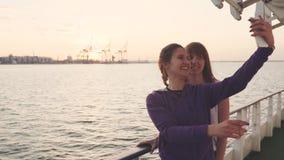 Duas mulheres bonitas que fazem a foto do selfie ao apreciar férias em um barco video estoque