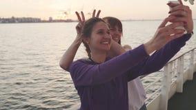 Duas mulheres bonitas que fazem a foto do selfie ao apreciar férias em um barco filme