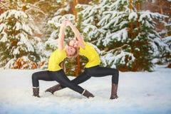 Duas mulheres bonitas que fazem a ioga fora na neve imagens de stock
