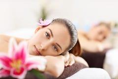 Duas mulheres bonitas que obtêm a massagem nos termas Foto de Stock