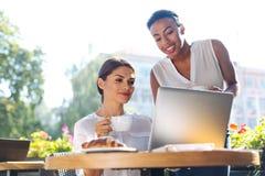 Duas mulheres bonitas que olham a apresentação no portátil Foto de Stock