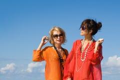 Duas mulheres bonitas que ouvem escudos foto de stock royalty free