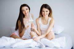Duas mulheres bonitas que sentam-se em uma cama e em um olhar na câmera Fotografia de Stock Royalty Free