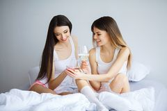 Duas mulheres bonitas que sentam-se em uma cama e em um olhar na câmera Foto de Stock