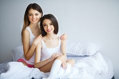 Duas mulheres bonitas que sentam-se em uma cama e em um olhar na câmera Foto de Stock Royalty Free