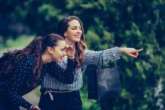 Duas mulheres bonitas que têm uma conversação de relaxamento ao andar no parque após a compra imagem de stock royalty free