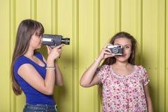 Duas mulheres bonitas que usam a câmera da câmara de vídeo e do filme do vintage contra a parede amarela fotos de stock royalty free