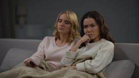Duas mulheres cansados que olham o programa longo da tevê da perfuração em casa e que dormem, noite video estoque