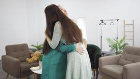 Duas mulheres caucasianas felizes nos vestidos se abraçando bem Brunette, garota abraçando sua amiga grávida Empresa feminina vídeos de arquivo