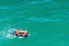 Duas mulheres caucasianos bonitas novas no banho de sol do biquini, espirrando e relaxando no colchão na água calma dos azuis cel fotografia de stock
