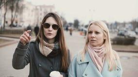 Duas mulheres caucasianos que conversam a caminhada na rua Amigas que andam junto no dia ensolarado do inverno Amigos que compart video estoque