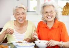 Duas mulheres chinesas sênior que sentam em casa comer Fotos de Stock Royalty Free