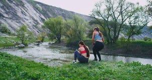 Duas mulheres com corpos de um ajuste têm exercícios de um exercício na natureza junto que se motivam quando tome algum fresco video estoque