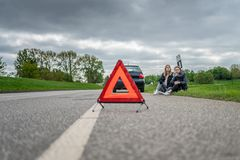 Duas mulheres com a divisão do carro que senta-se na borda da estrada e na ajuda de espera foto de stock