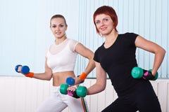 Duas mulheres da aptidão que levantam dumbbells Imagem de Stock