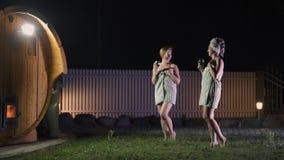 Duas mulheres das amigas que bebem o vinho tinto do outsite dos vidros perto de uma sauna m?vel de madeira que veste apenas toalh filme