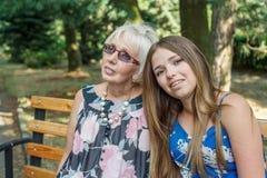 Duas mulheres das gerações diferentes que sentam-se em um banco no verão Foto de Stock Royalty Free