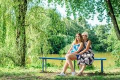 Duas mulheres das gerações diferentes que sentam-se em um banco perto de uma lagoa no verão Foto de Stock