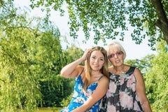Duas mulheres das gerações diferentes que sentam-se em um banco perto de uma lagoa no verão Fotos de Stock Royalty Free