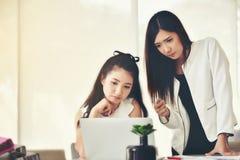 Duas mulheres de negócio asiáticas são estadas relacionadas sobre o negócio com o i fotos de stock