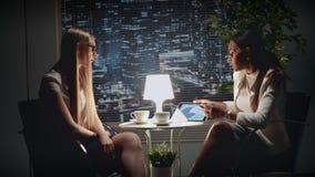 Duas mulheres de negócio multirraciais que discutem os resultados de seu trabalho com a tabela video estoque