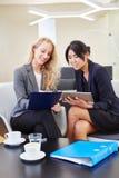 Duas mulheres de negócio novas com tablet pc foto de stock