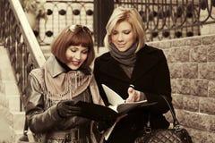 Duas mulheres de negócio novas da forma com um dobrador Fotografia de Stock Royalty Free