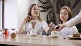 Duas mulheres de negócio novas estão sentando-se em um café É uma reunião do amigo As meninas estão sentando-se no café na tabela filme