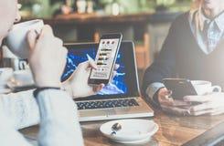 Duas mulheres de negócio novas que sentam-se na tabela no café A mulher olha gráficos, diagramas e cartas na tela do smartphone Imagem de Stock