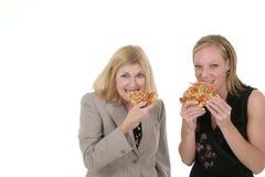 Duas mulheres de negócio que comem a pizza Imagem de Stock