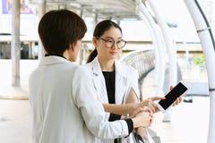 Duas mulheres de negócio que encontram-se, mulheres de negócio que usam o PC da tabuleta fotografia de stock