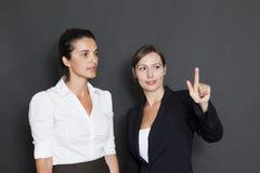 Duas mulheres de negócio que usam tecnologias novas foto de stock