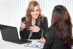 Duas mulheres de negócios amigáveis que sentam e que discutem ideias novas Fotografia de Stock