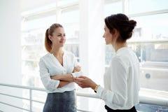 Duas mulheres de negócios atrativas encontraram-se no escritório interior e pararam-se à fala sobre a reunião com clientes, Imagens de Stock Royalty Free