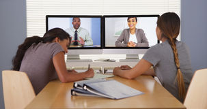 Duas mulheres de negócios multi-étnicas que falam com a tabuleta na mesa Imagens de Stock