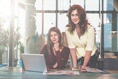 Duas mulheres de negócios novas estão trabalhando no escritório A primeira mulher senta-se na tabela e olha-se a tela do portátil imagens de stock royalty free