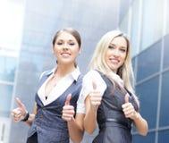 Duas mulheres de negócios novas que mantêm os polegares imagem de stock