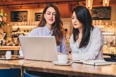 Duas mulheres de negócios novas que sentam-se no café na tabela e que usam o portátil, funcionamento, blogging As meninas estão o Imagens de Stock