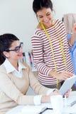 Duas mulheres de negócios novas que trabalham com a tabuleta digital nela offic Fotos de Stock Royalty Free