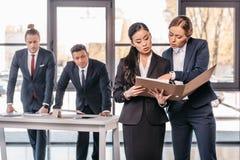 Duas mulheres de negócios novas que trabalham junto com o dobrador quando homens de negócios que estão atrás Fotografia de Stock Royalty Free
