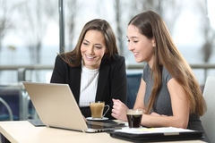 Duas mulheres de negócios que trabalham na linha em uma barra fotografia de stock