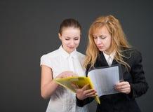 Duas mulheres de negócios de fala com originais. Fotos de Stock Royalty Free