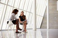 Duas mulheres de negócios que encontram-se na recepção do escritório moderno Imagem de Stock Royalty Free